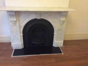 Victorian arched fireplace after restoration with a honed granite hearth