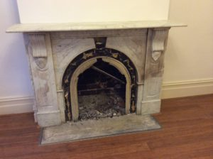 Victorian arched fireplace before restoration