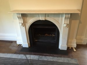 Victorian arched fireplace after restoration with a honed granite hearth and a trim around the firebox