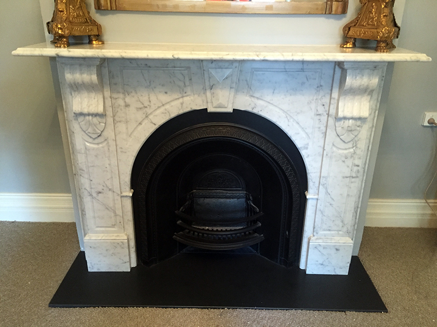 Victorian style arched custom made marble fireplace with a honed granite hearth